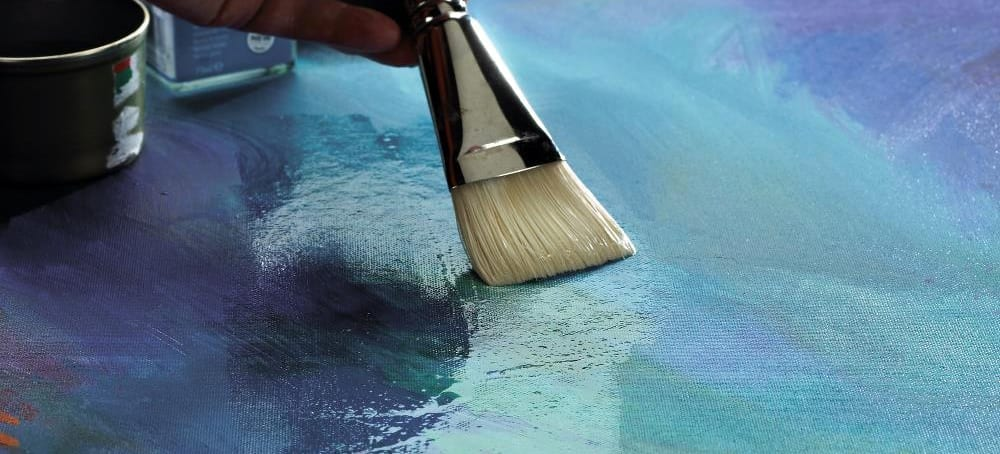 Paintbrush putting varnish on a finished painting