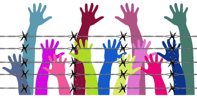 Colourful hands reaching behind barbed wire