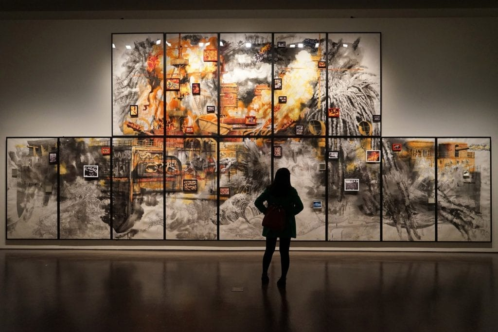 person standing in front of paintings in a gallery